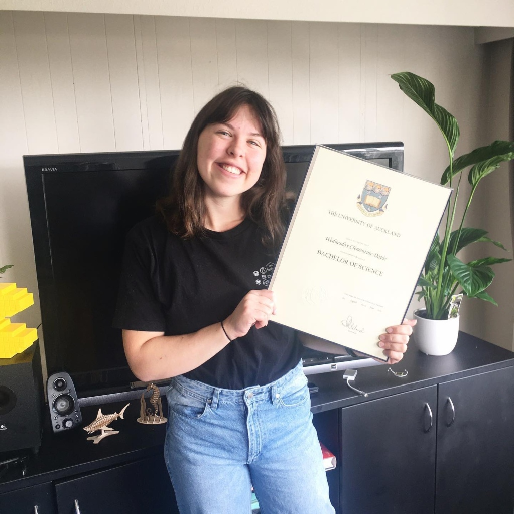 Image description: me holding my bachelors degree in my living room